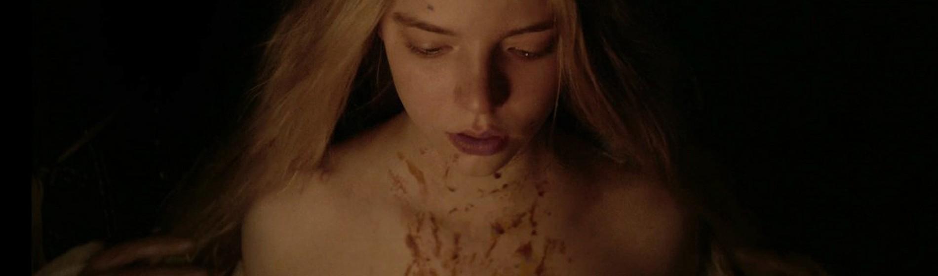 Imagem do filme A Bruxa, ou The Witch. Na imagem uma jovem nua e ensanguentada aparece na frente de um fundo preto.