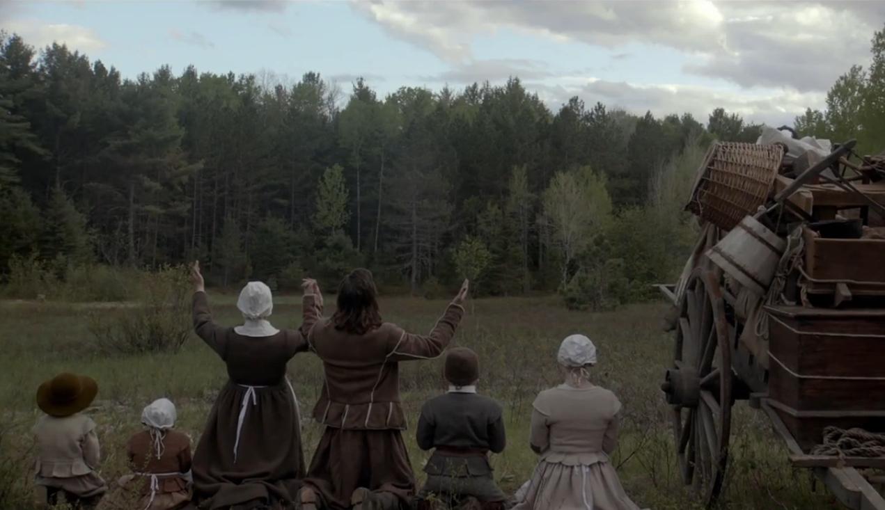 Imagem do filme A Bruxa, ou The Witch. Na imagem uma família está de joelhos, clamando aos céus na frente de um campo vazio.