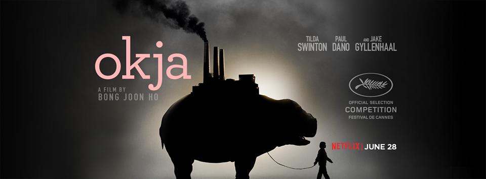 Mija leva Okja por uma corda, enquanto uma indústria se apoio sob as costas do animal. Cartaz de divulgação do filme.