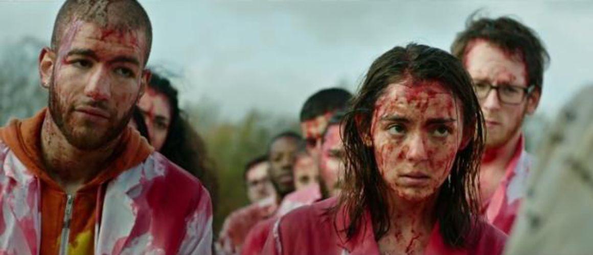 Justine e Adrien, em seus jalecos brancos, estão de pé e cobertos de sangue no filme 'Raw'.