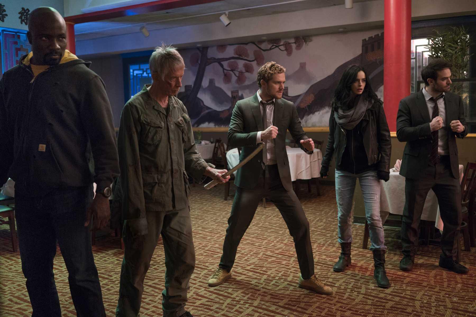 Cena de Os Defensores, ou The Defenders, série da Marvel e Netflix. Na cena, estão em posição de combate: Luke Cage, Stick, Danny Rand, Jessica Jones e Matt Murdock