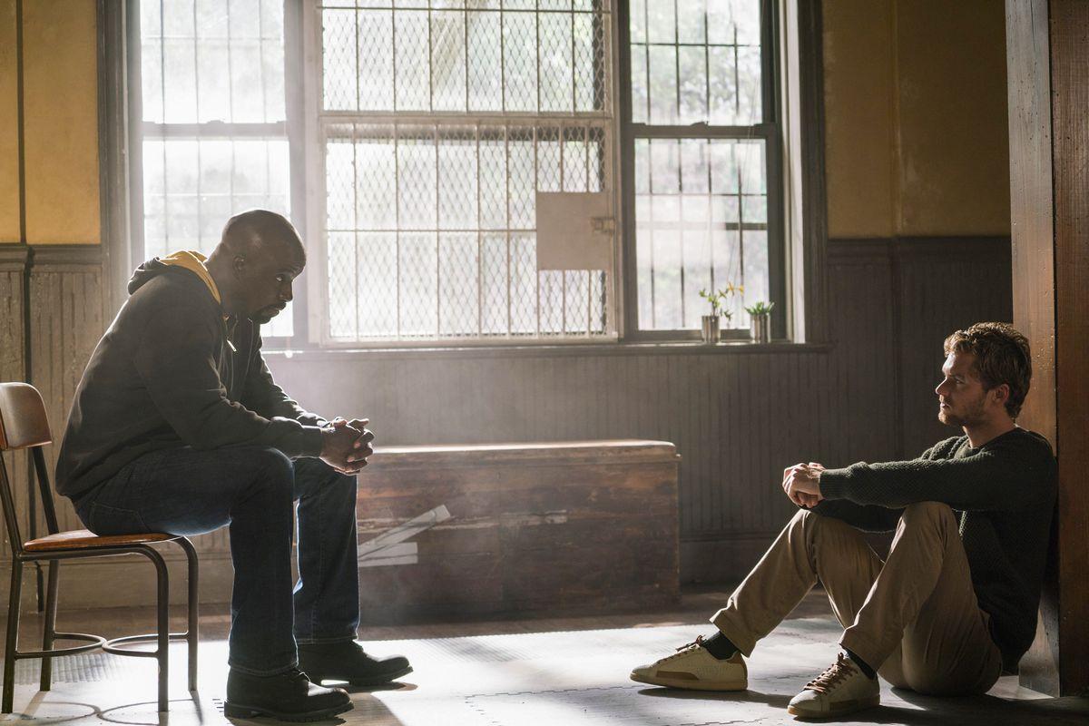Cena de Os Defensores, ou The Defenders, série da Marvel e Netflix. Na cena, Luke Cage está sentado em uma cadeira na frente de Danny Rand, o Punho de Ferro, que está sentado no chão.