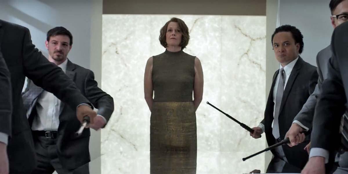 Cena de Os Defensores, ou The Defenders, série da Marvel e Netflix. Na cena, Alexandra, interpretada por Sigourney Weaver, está parada de forma ameaçadora, enquanto capangas armados avançam sob seu comando.