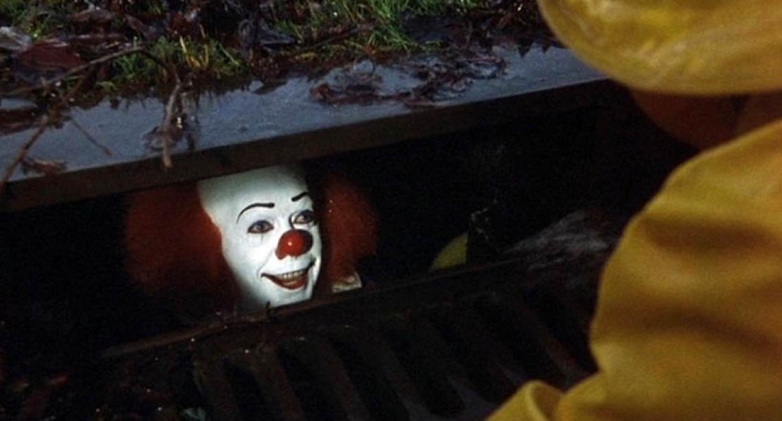 Pennywise, o Palhaço, olha de dentro de um bueiro para uma criança com capa de chuva amarela. O vilão aparece no filme It - A Coisa, baseado em livro de Stephen King.