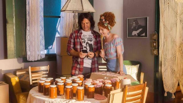 Imagem de Divórcio mostra Noeli e Júlio felizes diante de uma mesa cheia de potes do molho de tomate que acabaram de inventar. No fundo, há um quadro com a foto do astro do rock Kurt Cobain.