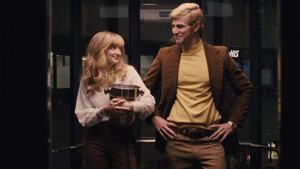 Cena de A Guerra dos Sexos em que Marilyn, a amante, e Larry, o esposo de Billie Jean King, se esbarram em um elevador.