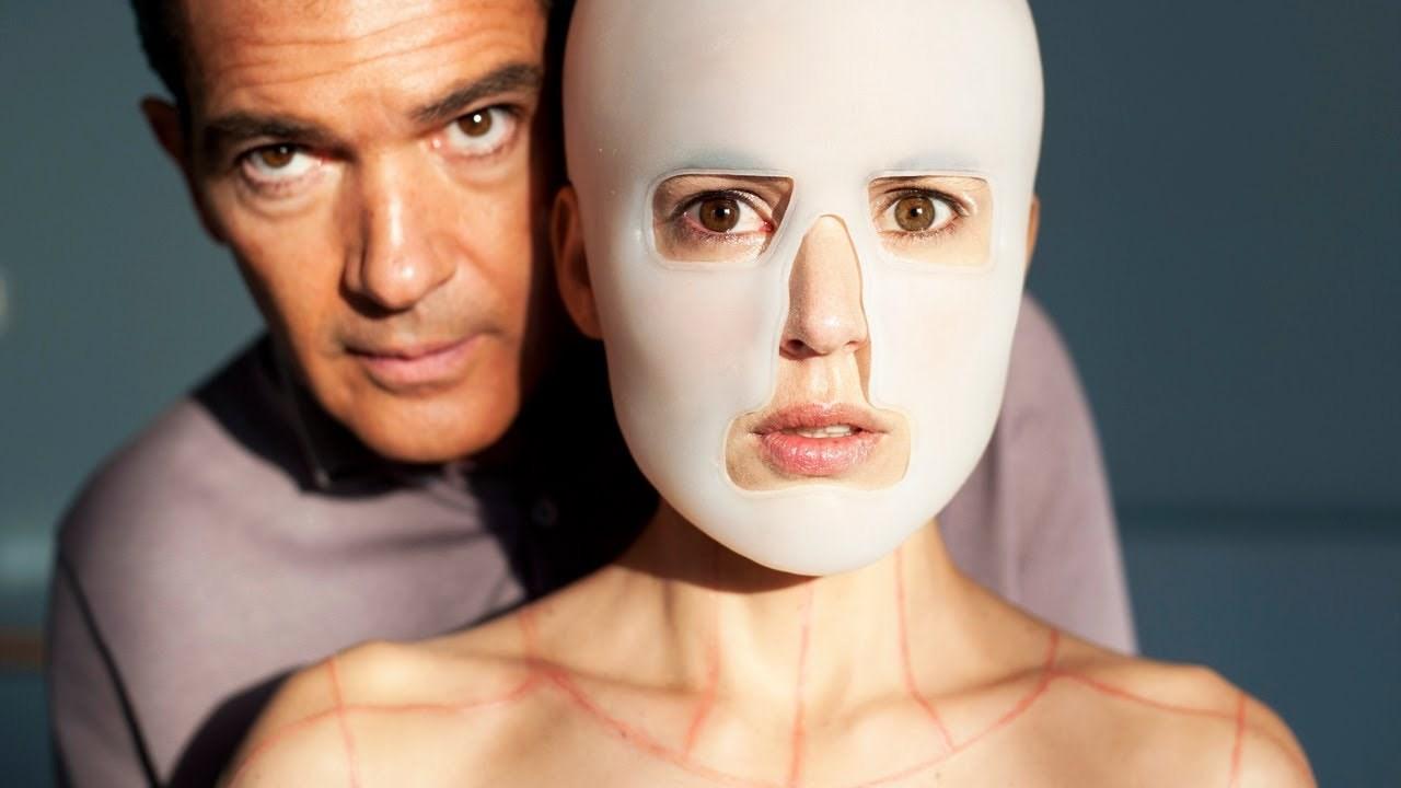 Imagem do filme A Pele que Habito, ou La Piel que Habito, ou ainda The Skin I Live In. A imagem mostra o rosto de uma jovem coberto por uma máscara branca, enquanto um homem s aproxima por trás.