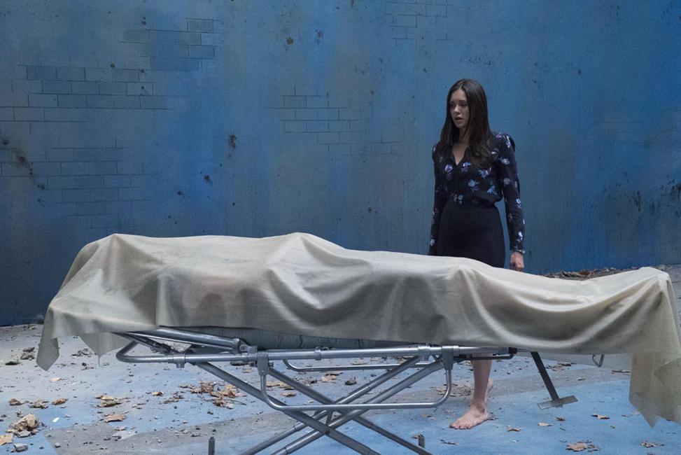 Cena do filme Além da Morte, ou Flatliners, remake do filme cult Linha Mortal. A cena mostra uma jovem descalça em frente a um cadáver coberto por um lençol branco.