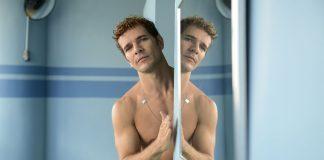 Imagem do filme Aos Teus Olhos, parte do Festival do Rio de 2017. A imagem mostra um homem com trço nu inclinado para dentro de uma porta, enquanto sua imagem é refletida em um espelho.