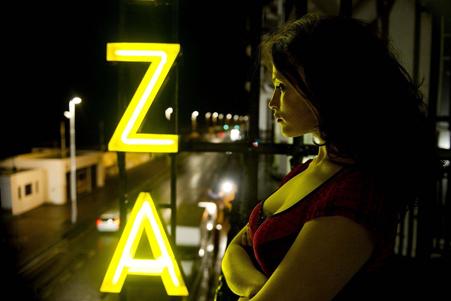 Imagem do filme Byzantium - Uma Vida Eterna. A Imagem mostra Clara, interpretada por Gemma Arteton, parada na sacada do hotel Byzantium, de noite.