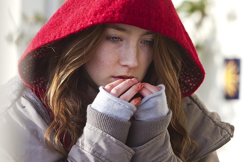 Imagem do filme Byzantium - Uma Vida Eterna. A Imagem mostra Eleanor, interpretada por Saoirse Ronan, em primeiro plano, com dedos ensaguentados nos lábios, e um capuz vermelho cobrindo sua cabeça;