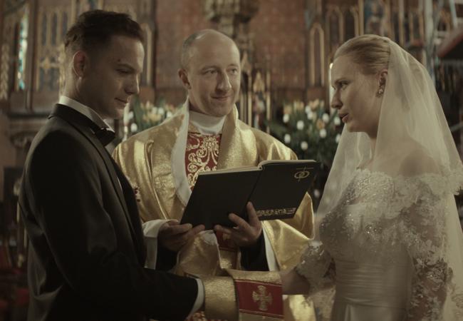 Imagem do filme polonês Demon, de Marcin Wrona. A imagem mostra um casal, em frente a um padre, dentro de uma igreja, se casando.