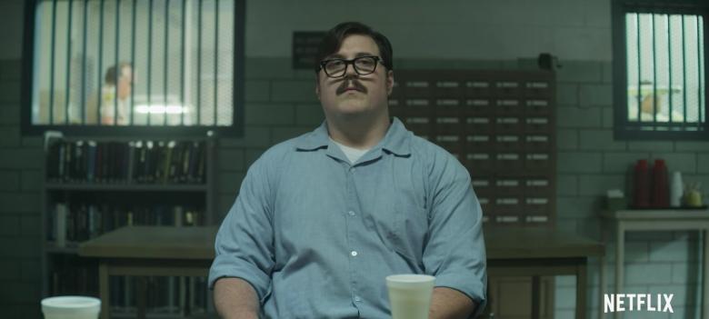 Imagem da série Mindhunter, da Netflix. A imagem mostra o assassino Edmund Kemper, interpretado por Cameron Britton, com uniforme de prisão em uma sala de visitas.