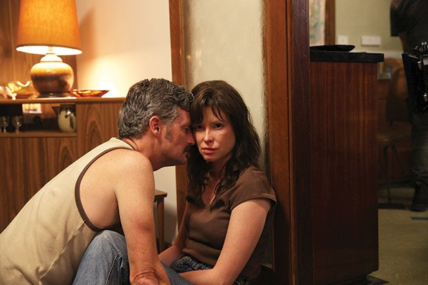 Imagem do filme australiano Hounds of Love, ou Predadores do Amor. A imagem mostra um casal sentado no chão; a mulher parece nervosa, enquanto o homem tenta acalmá-la.