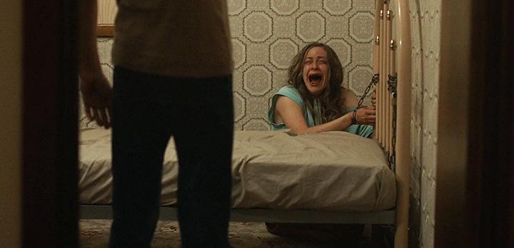 Imagem do filme australiano Hounds of Love, ou Predadores do Amor. A imagem mostra uma jovem, ferida e acorrentada em uma cama, gritando enquanto um homem se aproxima.