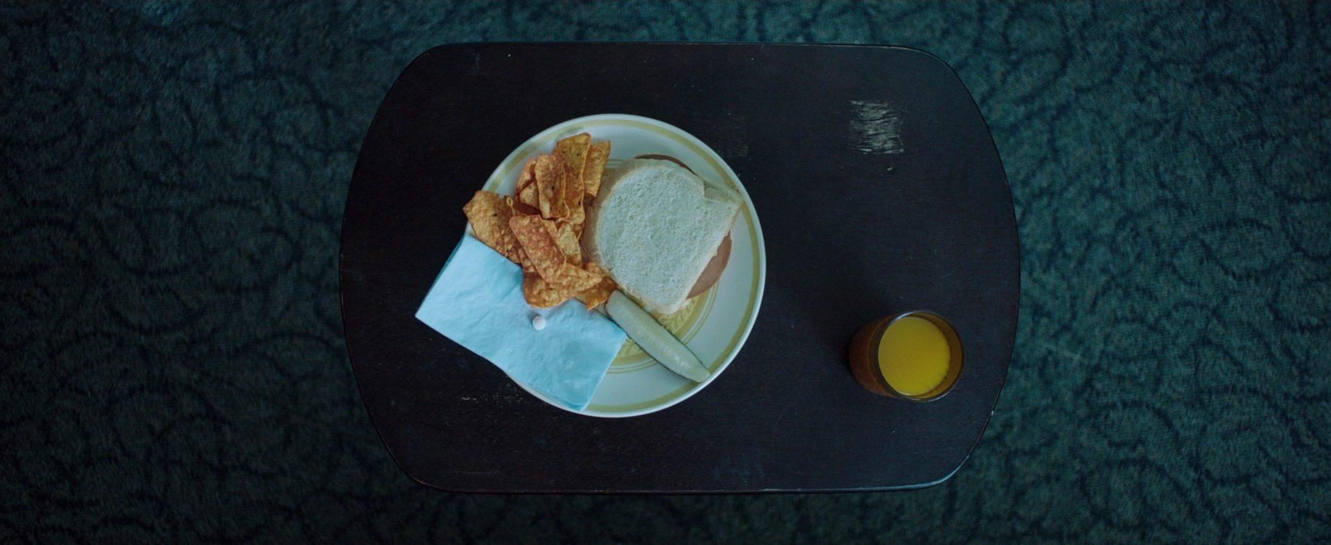 Cena do filme Corrente do Mal, também conhecido como It Follows. A cena mostra uma prato de comida sobre uma mesa preta.