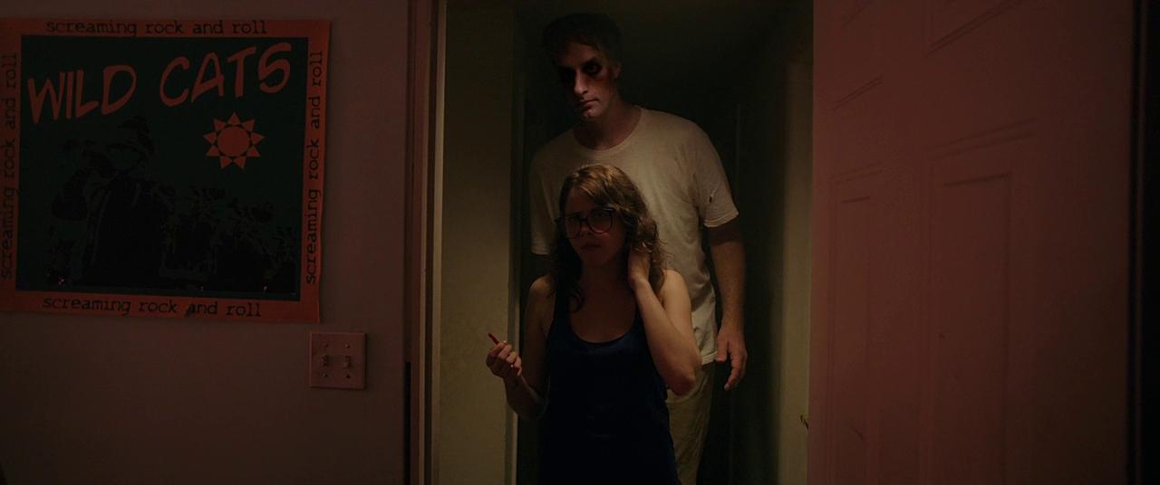 Imagem do filme Corrente do Mal, ou It Follows. A imaem motra uma jovem parada em uma porta, enquanto um homem muito alto se aproxima por trás.
