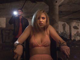 Cena do filme Corrente do Mal, também conhecido como It Follows. A cena mostra uma jovem amarrada em uma cadeira, enquanto um jovem segura uma lanterna ao fundo.