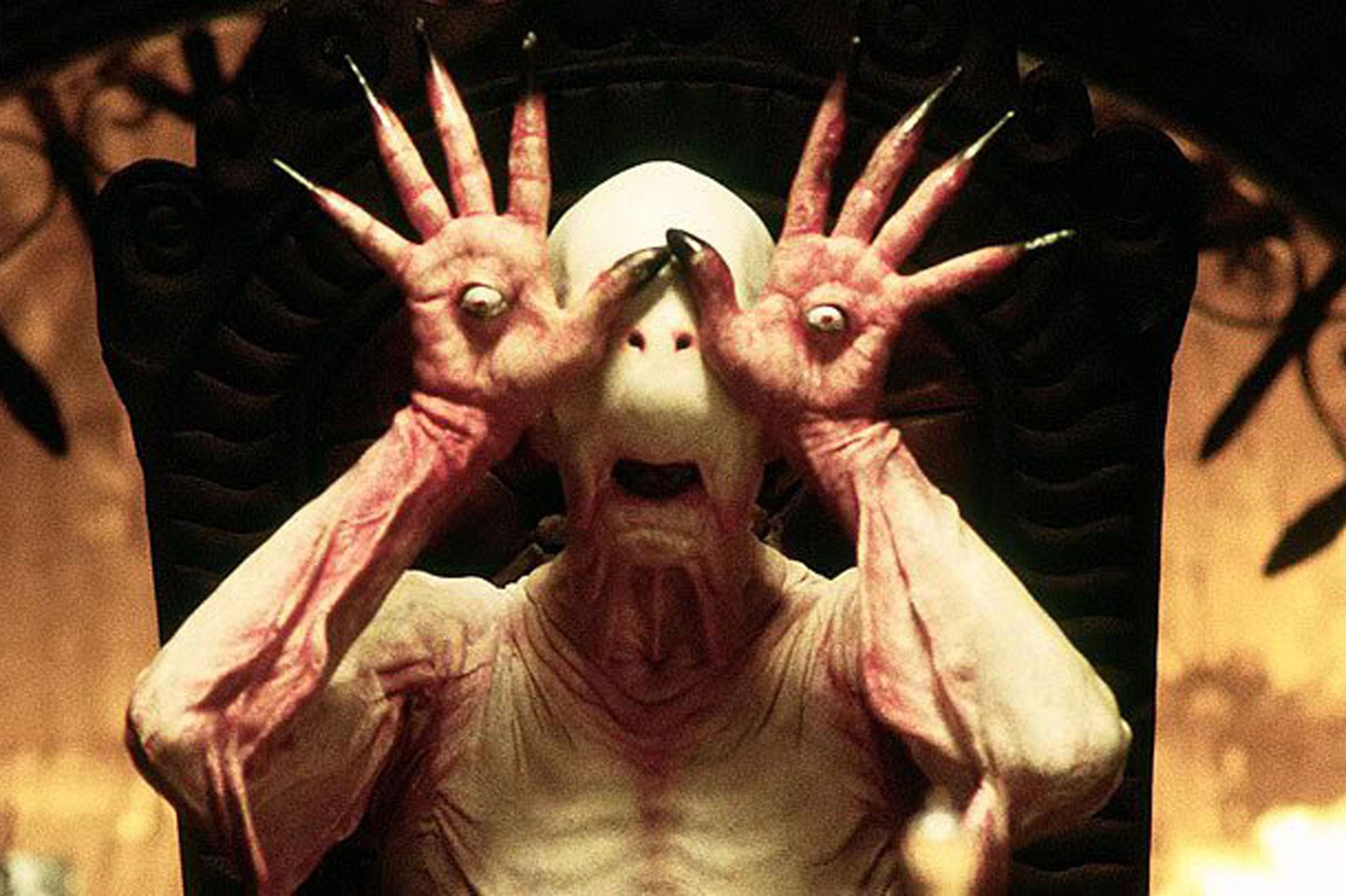 Image do filme 'O Labirinto do Fauno', também conhecido como 'Pan's Labyrinth', que mostra o Homem Pálido. Os olhos colados à mãos, enquanto as mãos estão sobre o rosto da criatura.