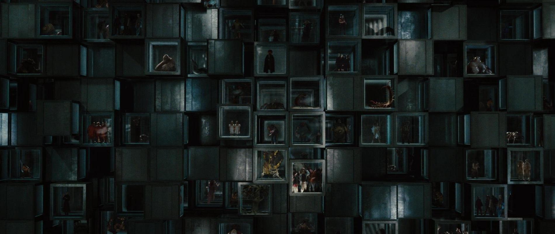 Cena do filme O Segredo da Cabana, ou The Cabin in the Woods. A imagem mostra dezenas de gaiolas de vidro suspensas prendendo monstros diversos.