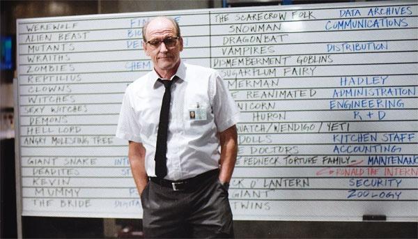 Cena do filme O Segredo da Cabana, ou The Cabin in the Woods. A imagem mostra um homem em uniforme de trabalho na frente de um quadro de apostas com nomes de monstros.