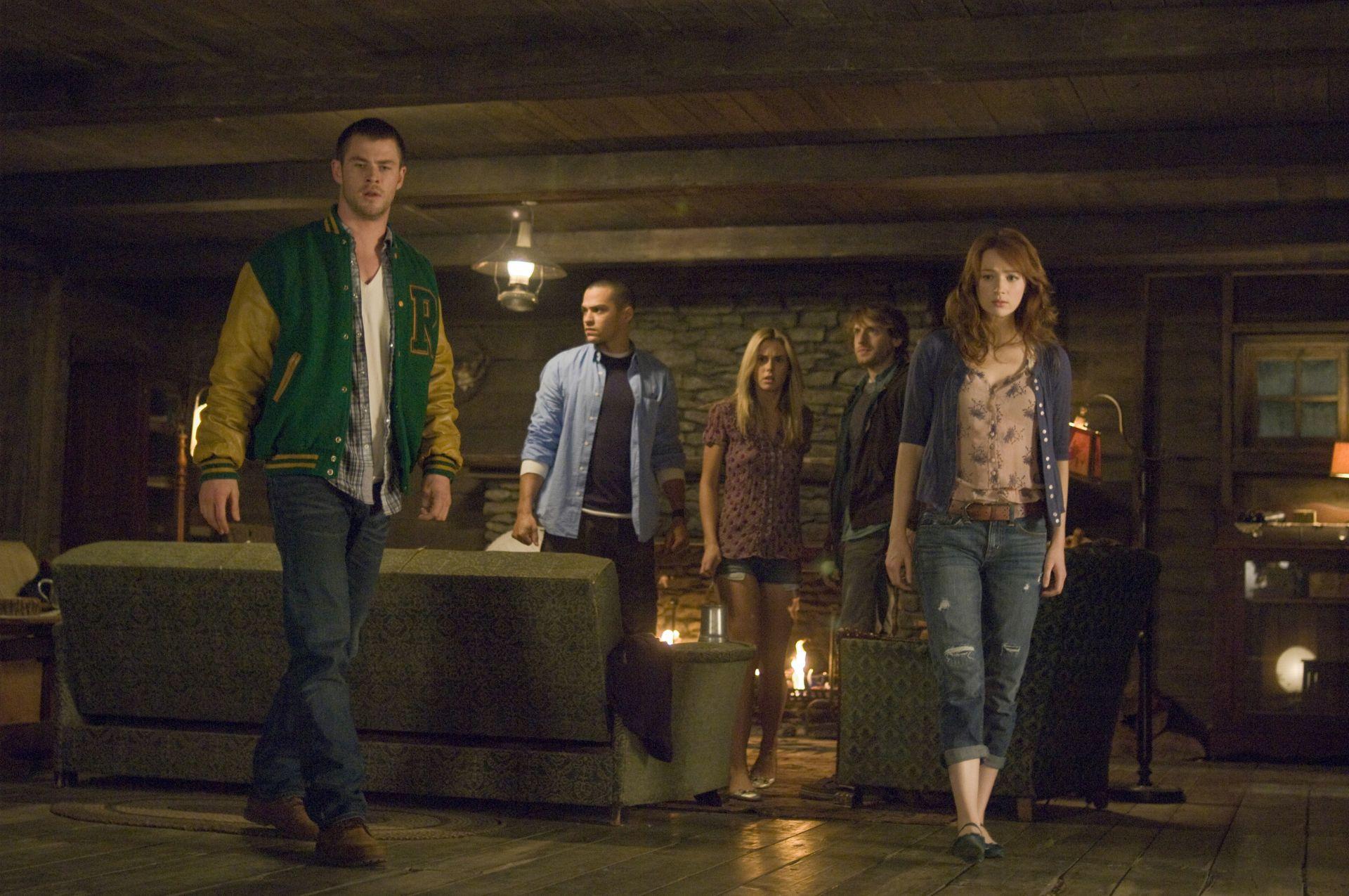 Cena do filme O Segredo da Cabana, ou The Cabin in the Woods. A imagem mostra cinco jovens em uma cabana de madeira.