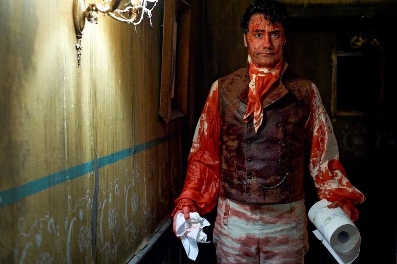 Imagem do filme O Que Fazemos nas Sombras, ou What we Do in the Shadows. A imagem mostra um vampiro coberto se sangue segurando um rolo de papel toalha para se limpar.