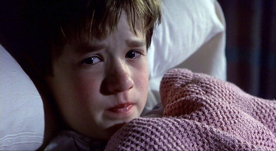 Cena do filme O Sexto Sentido, ou The Sixty Sense, que mostra um garotinho com medo deitado em uma cama e enrolado no cobertor.