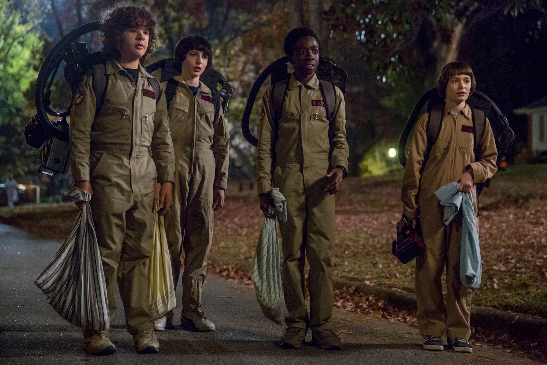 Cena de Stranger Things 2, em que Dustin, Mike, Lucas e Will estão fantasiados de Caça-Fantasmas.