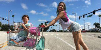 Imagem do filme The Florida Project, parte do Festival do Rio de 2017. A imagem mostra uma criança em um carrinho de supermercado, dirigido pela mãe da criança, aparentemente muito jovem.