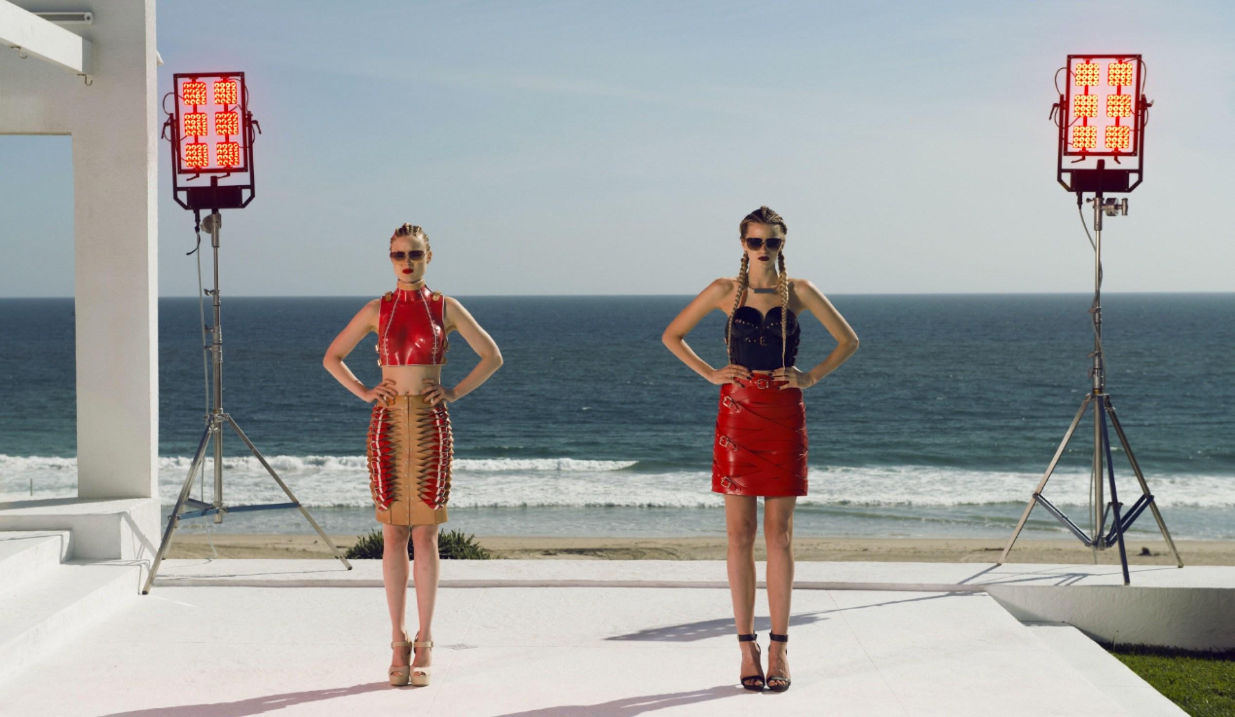 Imagem do filme The Neon Demon, ou Demônio Neon. A imagem mostra duas modelos posando em uma casa na frente do mar.