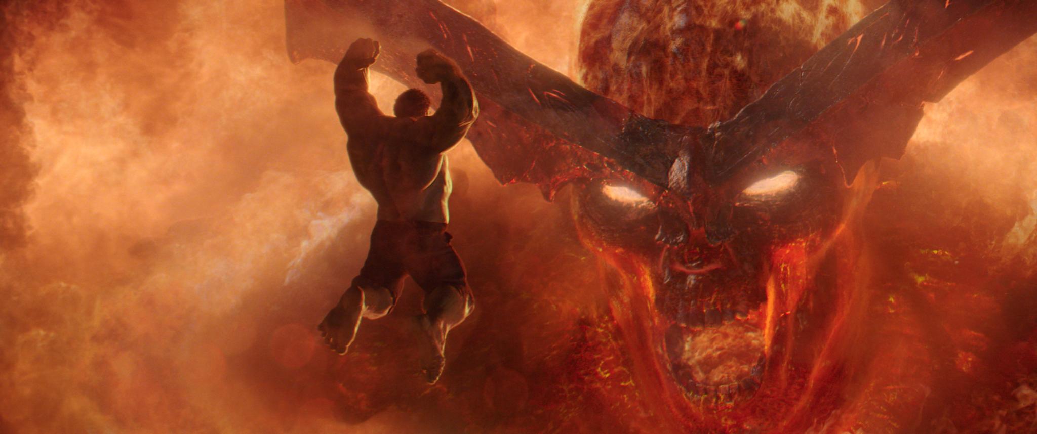 Surtur, o demônio de fogo, em sua forma de gigante, recebe um ataque de Hulk, à esquerda