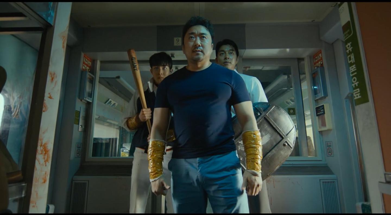 Imagem do filme Invasão Zumbi, ou Train to Busan, ou Busanhaeng. A imagem mostra três homens com bastões e coberturas amadoras nos braços, preparados para enfrentar os zumbis.
