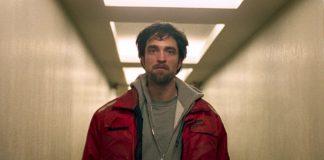 Imagem de Bom Comportamento mostra Robert Pattinson emum corredor branco e iluminado, usando uma jaqueta vermelha.