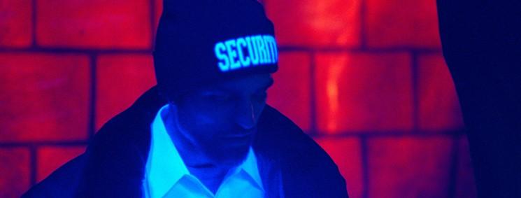 """Imagem de Bom Comportamento mostra Robert Pattinson iluminado por luz negra e usando um gorro escrito """"Security"""""""