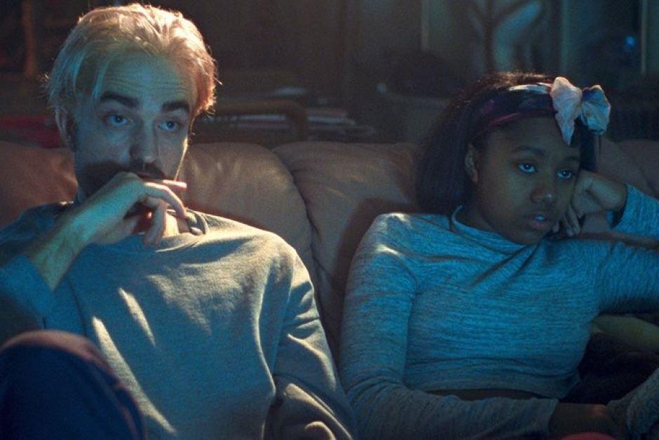 Imagem de Bom Comportamento mostra Pattinson e Taliah Webster sentados lado a lado em um sofá