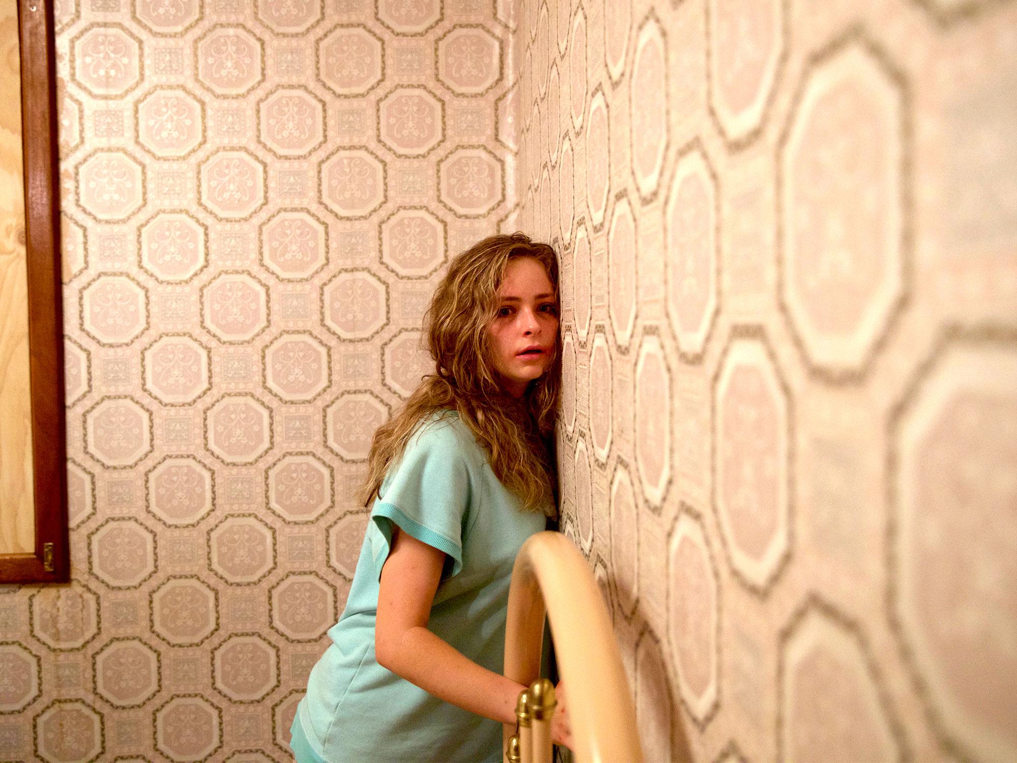 Imagem do filme australiano Hounds of Love, ou Predadores do Amor. A imagem mostra uma jovem, ferida e acorrentada em uma cama, com o rosto encostado em uma parede.