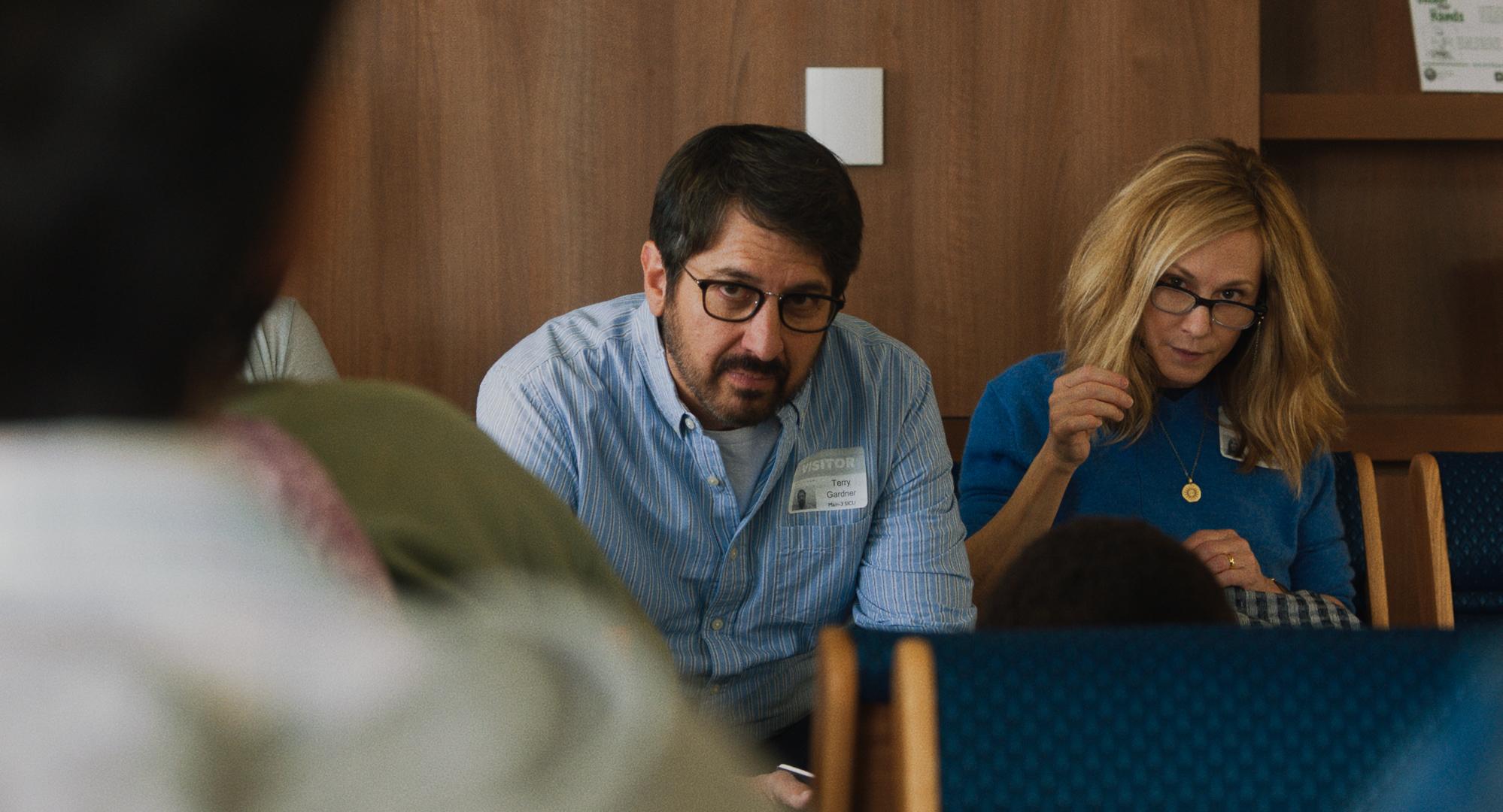 Imagem de Doentes de Amor mostra Terry (Ray Romano) e Beth (Holly Hunter) em uma sala de espera. Beth está tricotando.