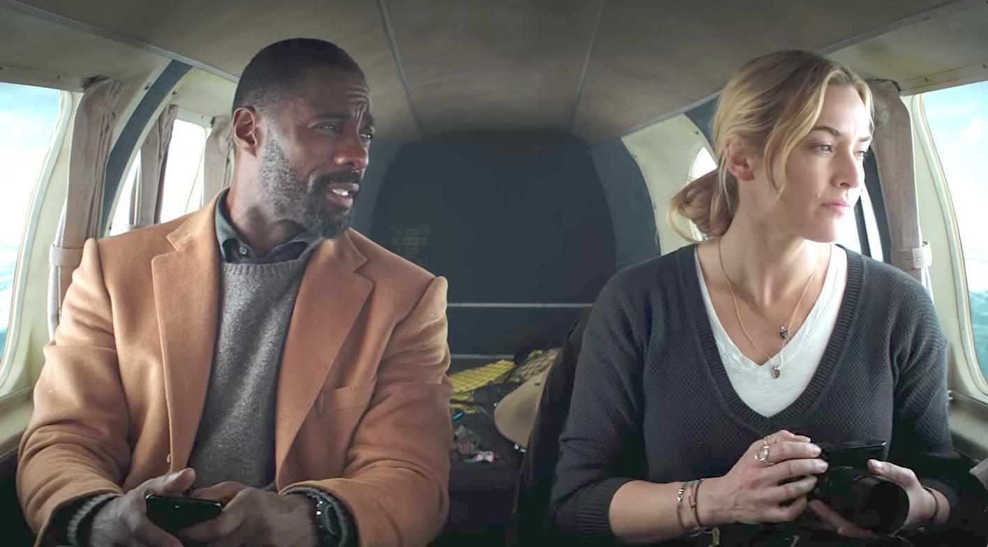 Imagem do filme Depois Daquela Montanha, ou The Mountain Between Us. A imagem mostra Ben (Idris Elba) e Alex (Kate Winslet) em um pequeno avião, antes da queda. Os personagens não se conhecem bem ainda.