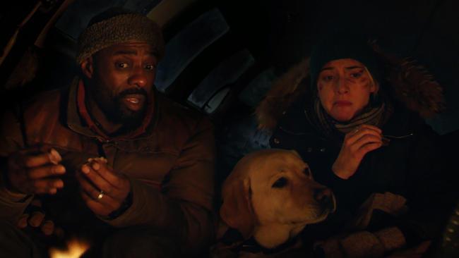 Imagem do filme Depois Daquela Montanha, ou The Mountain Between Us. A imagem mostra Ben (Idris Elba), Alex (Kate Winslet) e um cachorro, apertados na cabine de um avião, depois de sua queda.