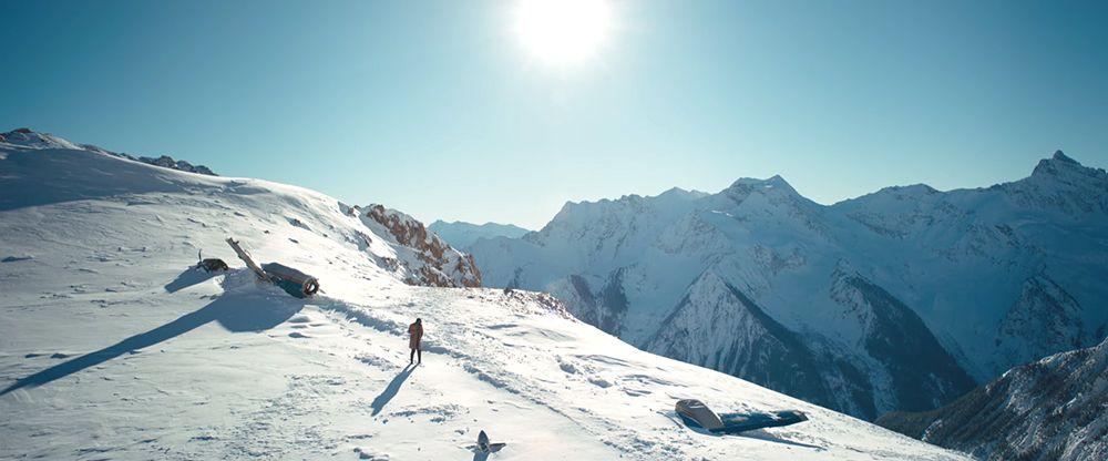 Imagem do filme Depois Daquela Montanha, ou The Mountain Between Us. A imagem mostra uma montanha, e nela os detroços de um avião, e Ben (Idris Elba) em pé.