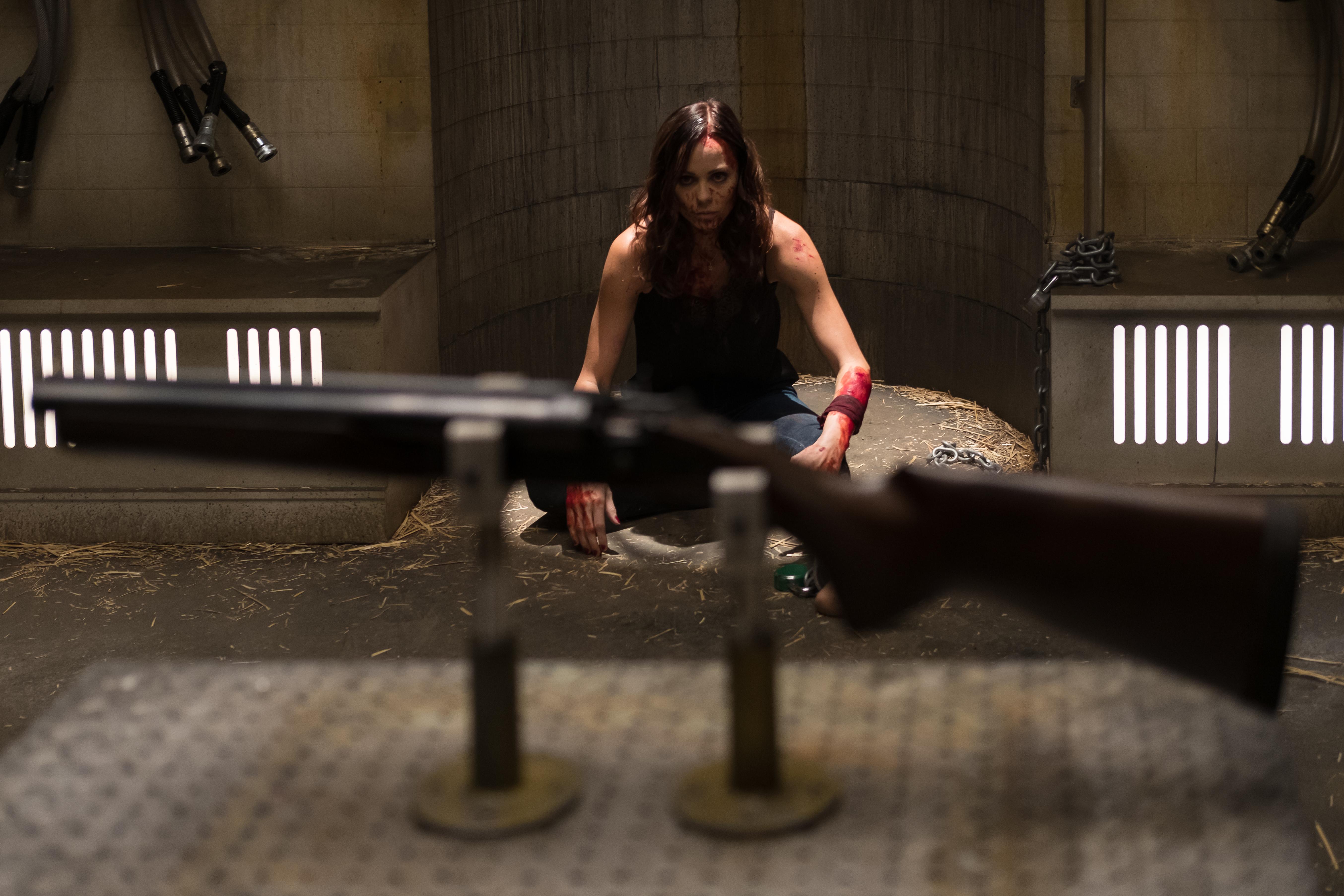 Imagem de Jogos Mortais: Jigsaw, que mostra uma das vítimas de John Kramer, ao fundo, olhando para uma espingarda em primeiro plano.