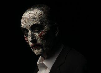 Imagem de divulgação de Jogos Mortais: Jigsaw, que mostra o ator Tobin Bell no papel do assassino John Kramer, usando a maquiagem de Billy, the Puppet.