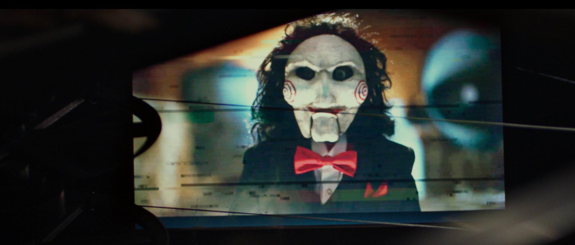 Imagem de Jogos Mortais: Jigsaw, que mostra Billy, the Puppet em uma gravação em VHS.