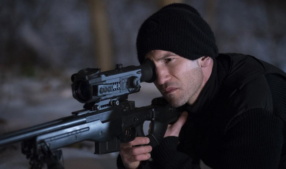 Jon Bernthal no papel de Frank Catle, o Justiceiro, ou Punisher, na série Marvel e Netflix, segura um rifle sniper.