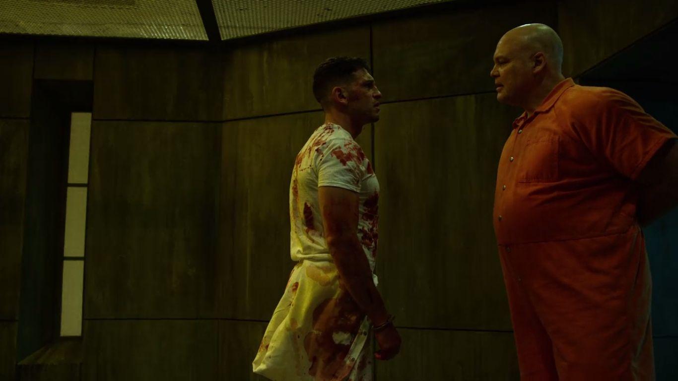Vicent D'Onofrio como o Rei do Crime, ou Kingpin, na série Demolidor, ou Daredevil, da Marvel com a Netflix, confronta Jon Bernthal no papel de Frank Catle, o Justiceiro, ou Punisher. ambos estão de pé, frente a frente, em uniformes de prisão.