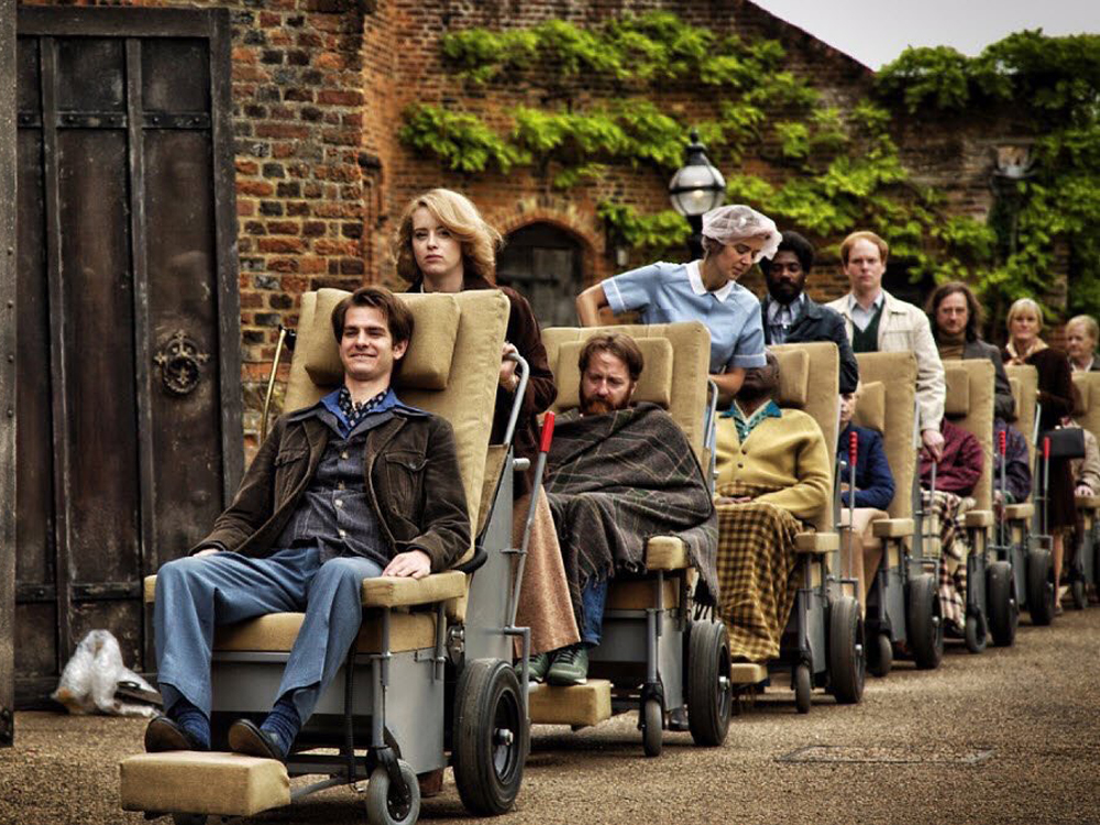 Imagem do filme Uma Razão Para Viver (Breathe). Na imagem, Robin Cavendish e outros pacientes que sofrem de polio saem do hospital em cadeiras de rodas adaptadas.