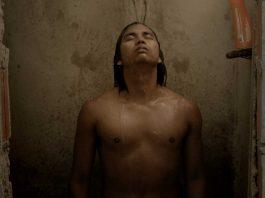 Imagem do filme Antes o Tempo Não Acabava , que mostra um homem de descendência indígena tomando banho em um banheiro extremamente pobre.