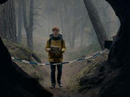 Imagem da série alemã Dark, da Netflix. A imagem mostra um adolescente com capa de chuva amarela na frente de uma caverna.