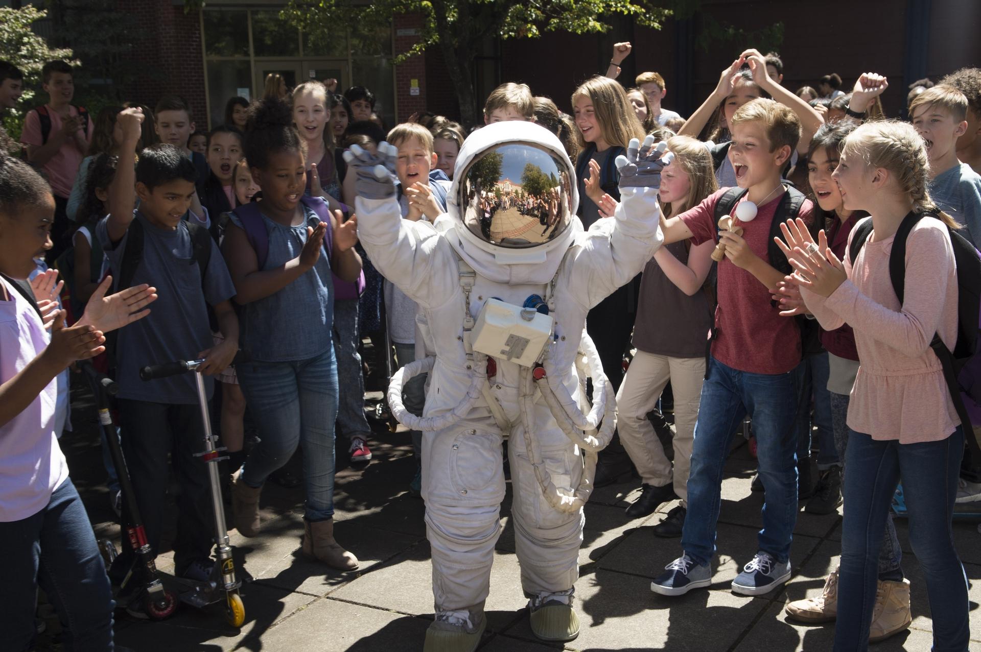 Imagem do filme Extraordinário (ou Wonder). Na imagem, Auggie usa uma roupa e capacete de astronauta e anda no meio dos outros alunos da escola, que o aclamam.